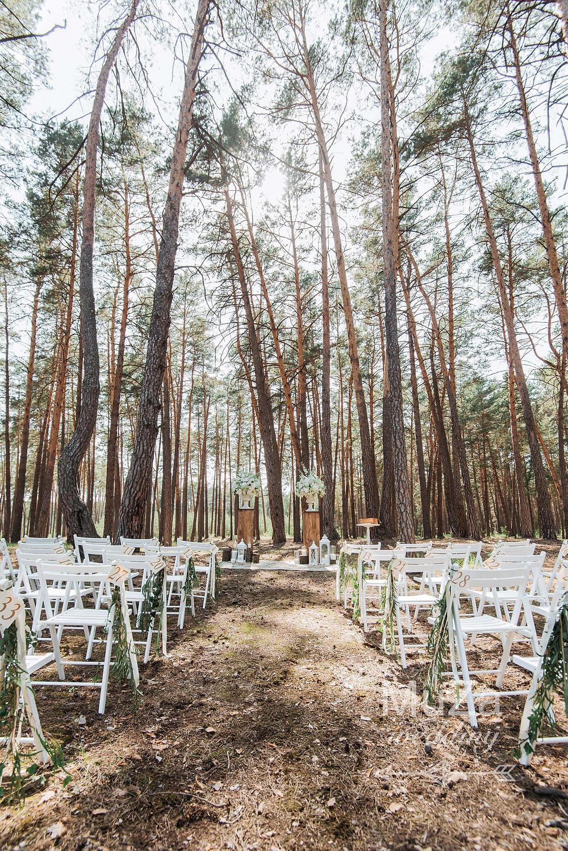 очень красивая свадебная церемония в лесу по Киевом, декор свадебной церемонии: складные садовые стулья, цветочные композиции из сирени, фонари, срубы, пеньки