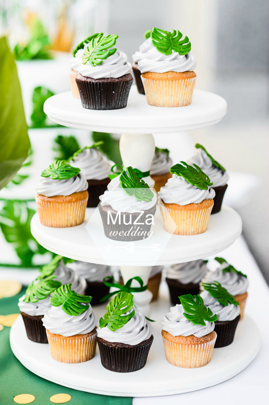 Свадебный кенди-бар (candy bar) от baby-bar на свадьбе в тропическом стиле: шоколадные и ванильные капкейки с белым кремом и зеленым листиком монстеры, свадебный декор, свадебный стиль, свадебное вдохновение