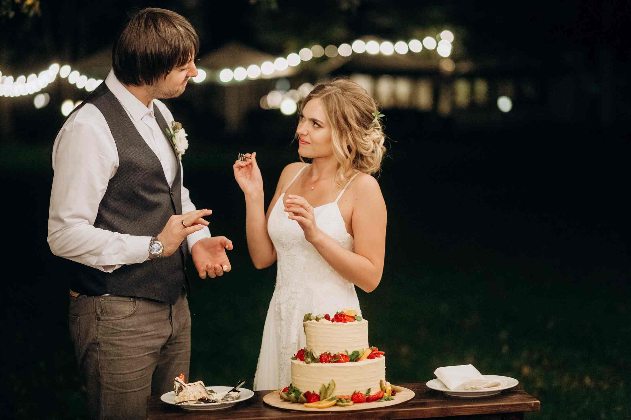 молодожены кормят друг друга тортом