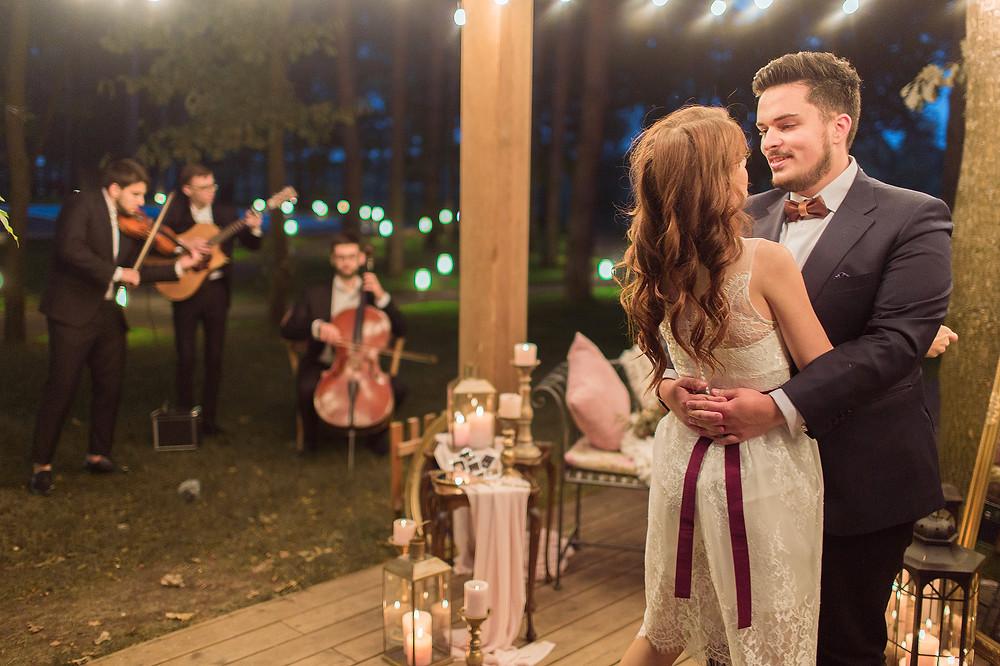 Романтический момент предложения руки и сердца: невеста и жених танцуют под звуки любимых композиций в исполнении инструментальной группы