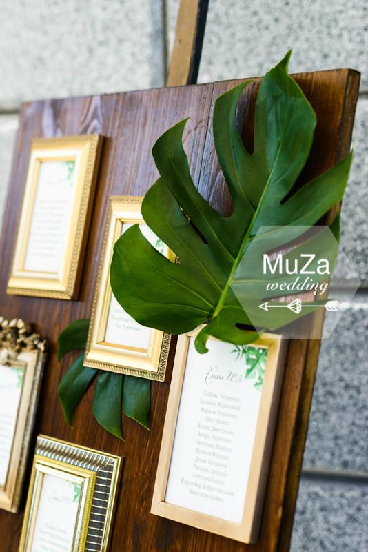 План рассадки гостей на свадьбе в тропическом стиле, деревянный мольберт и доска, золотые рамочки со списками гостей, листья монстеры. Оригинально и изысканно.