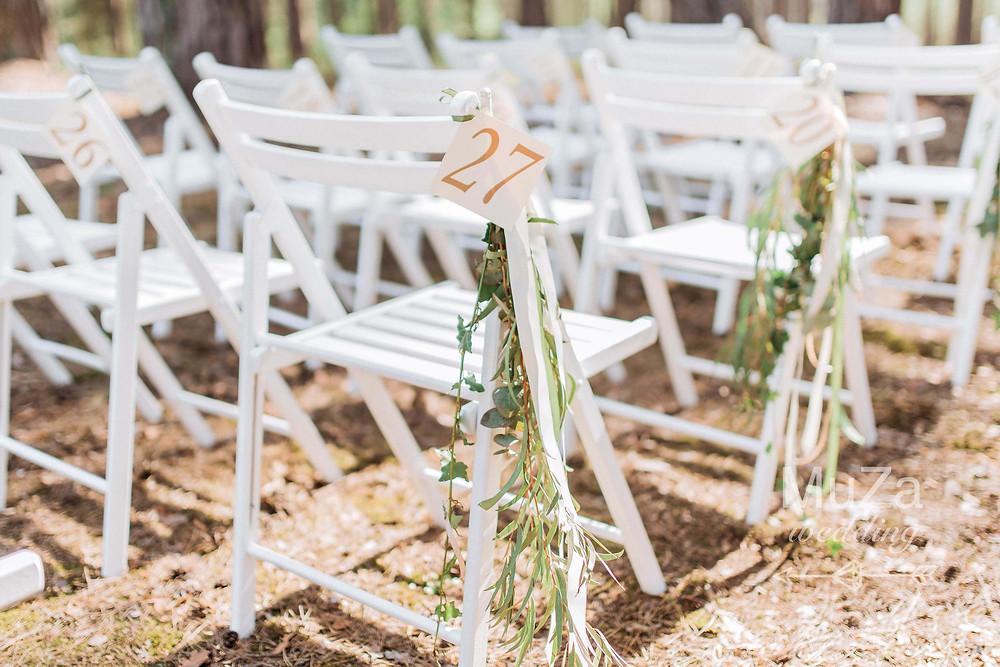 рассадка гостей на свадебной церемонии в лесу. Каждый гостевой стульчик украшен зеленью и номерком для рассадки