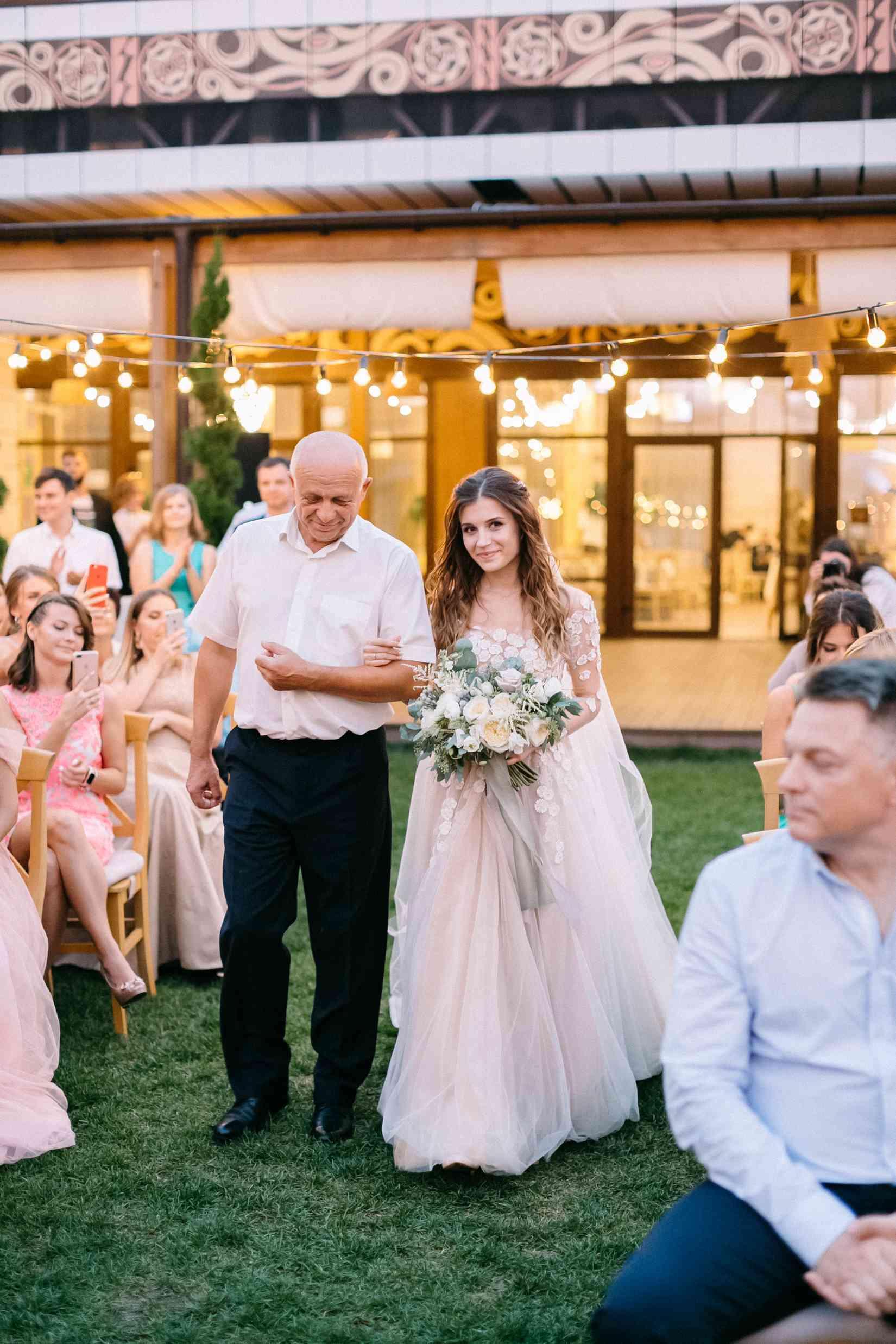 невеста с отцом выходят на церемонию
