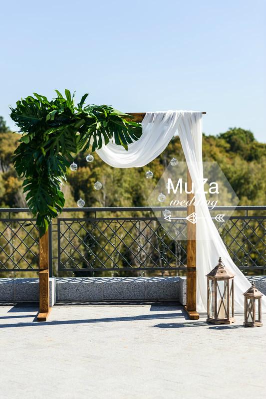 Красивая арка в тропическом стиле (wedding tropical), листья монстеры в сочетании с древесиной и тканевой драпировкой смотрятся очень свежо и стильно. А стеклянные шары и фонари создают целостность композиции. Организация свадьбы: MuZa-wedding, Киев, Украина
