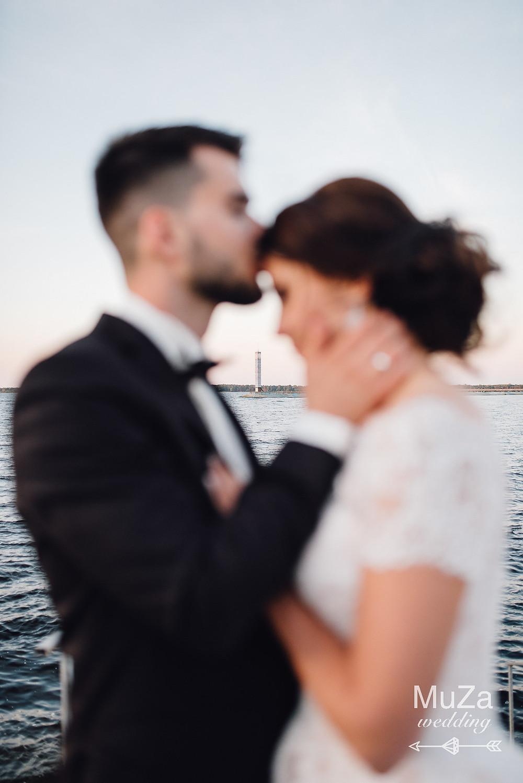 Пара молодоженов на фоне маяка на берегу моря