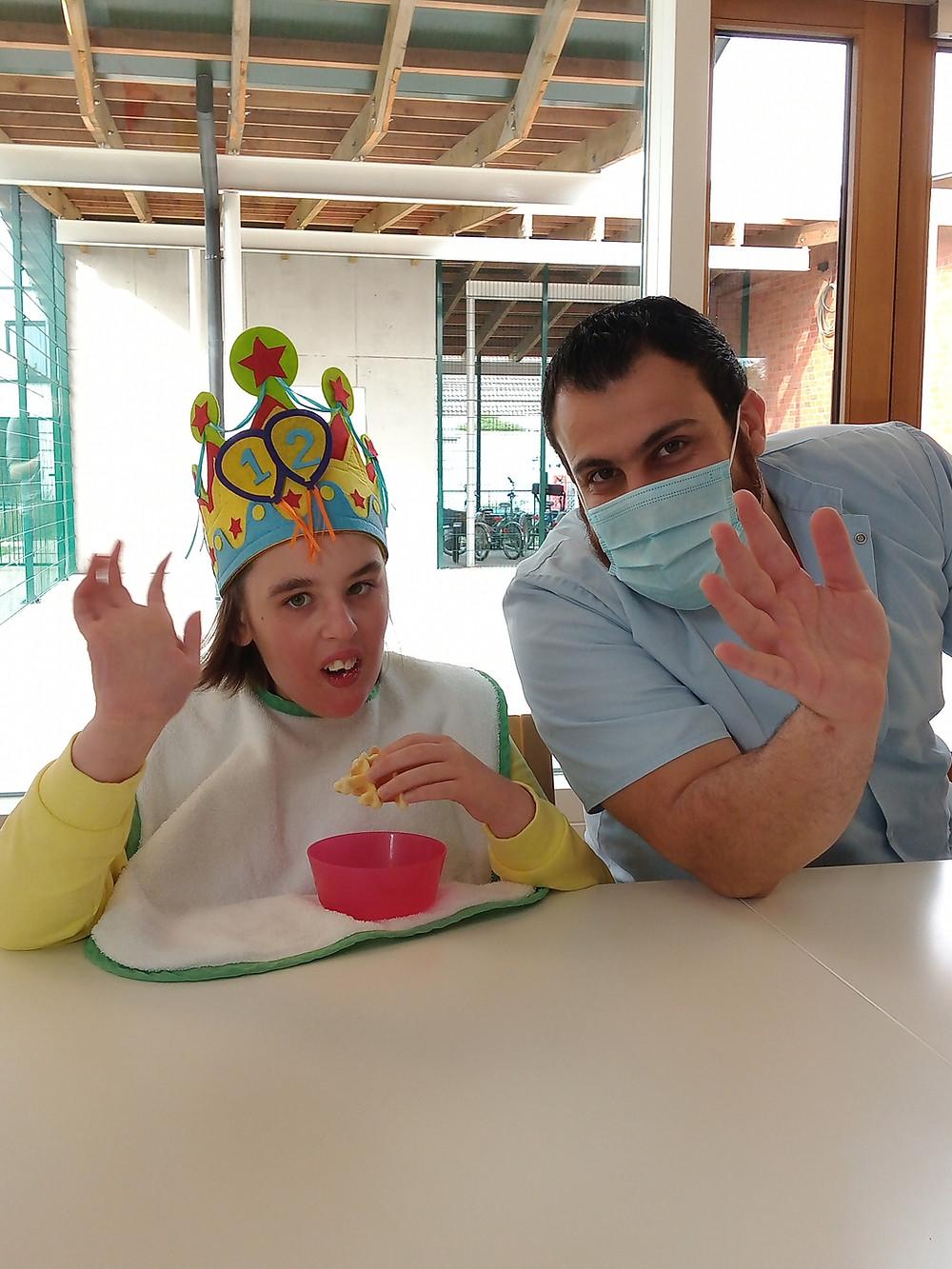 Stagiair helpt een jarige bewoner met kroon haar wafel opeten