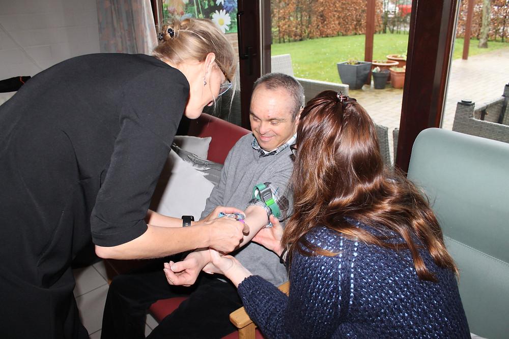 De dokter en verpleegster nemen een bloedafname van een bewoner in de leefgroep
