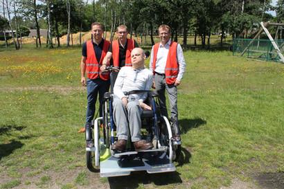 Enkele medewerkers van Rezinal maken een ritje met een bewoner die in een elektrische rolstoelfiets zit