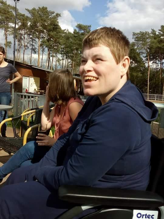 Lachende vrouw met Angelman syndroom in rolstoel