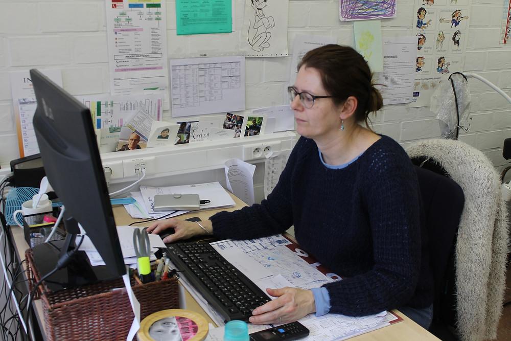 Verpleegkundige Inez werkt aan haar bureau