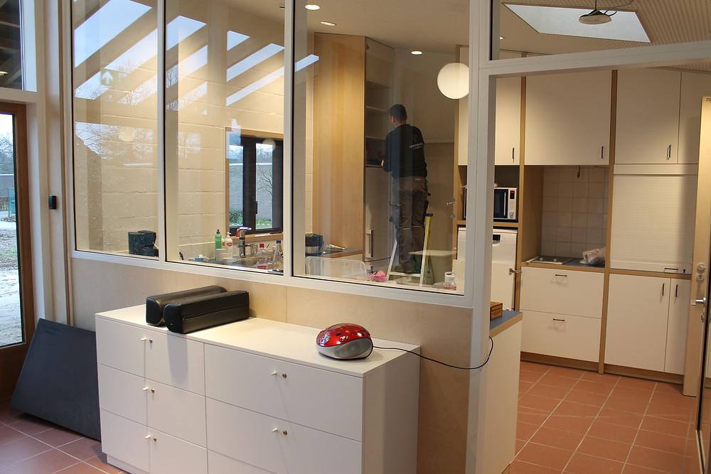 Een medewerker van de technische dienst installeert een keukenkast.
