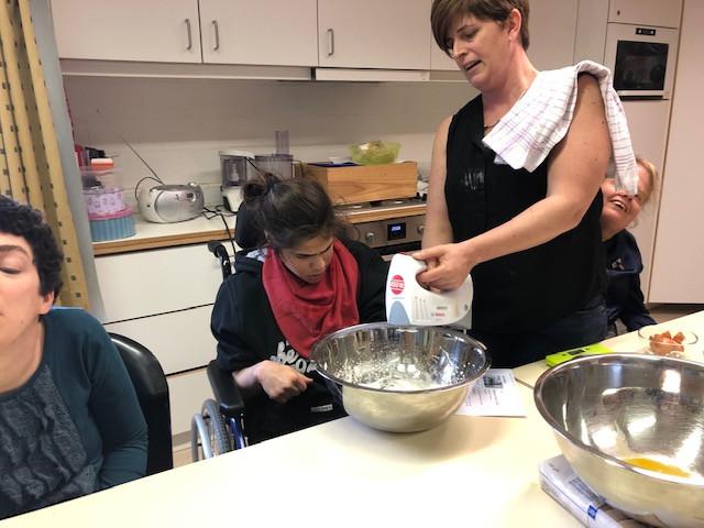 Ergotherapeut houdt de mixer vast tijdens een kookactiviteit met enkele bewoners
