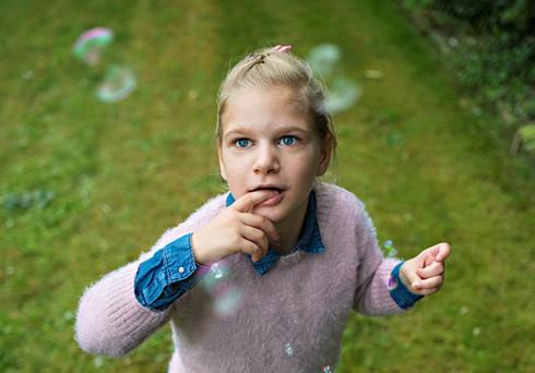 Meisje kijkt naar de bellen die rond haar vliegen in de tuin