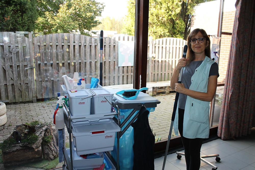 Poetsvrouw staat met een poetskar voor het raam in een leefgroep van Ter Heide