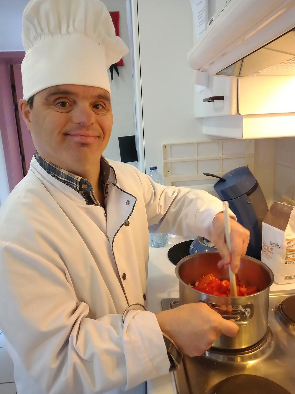 Bewoner van Ter Heide is aan het koken en draagt een koksoutfit