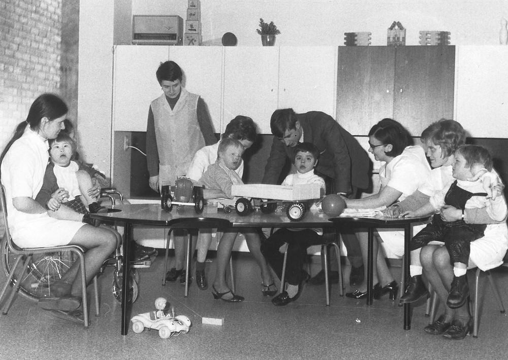 Verschillende medewerkers zitten rond een tafel met de eerste 5 bewoners van Ter Heide