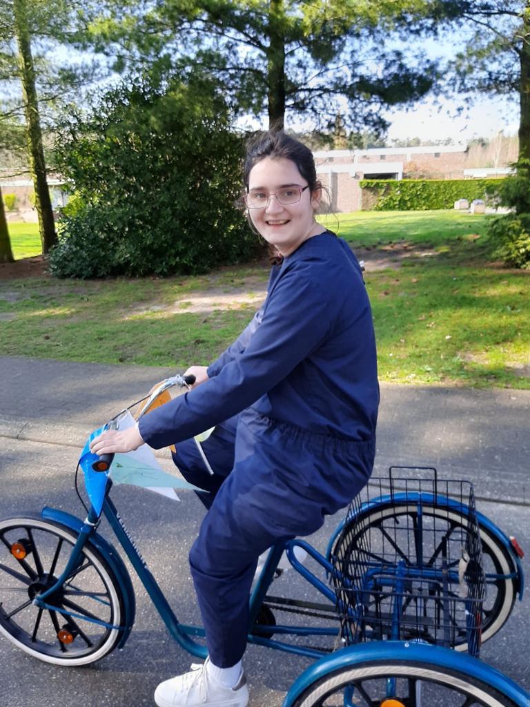 Meisje met een beperking fietst op een driewieler in de buitenlucht