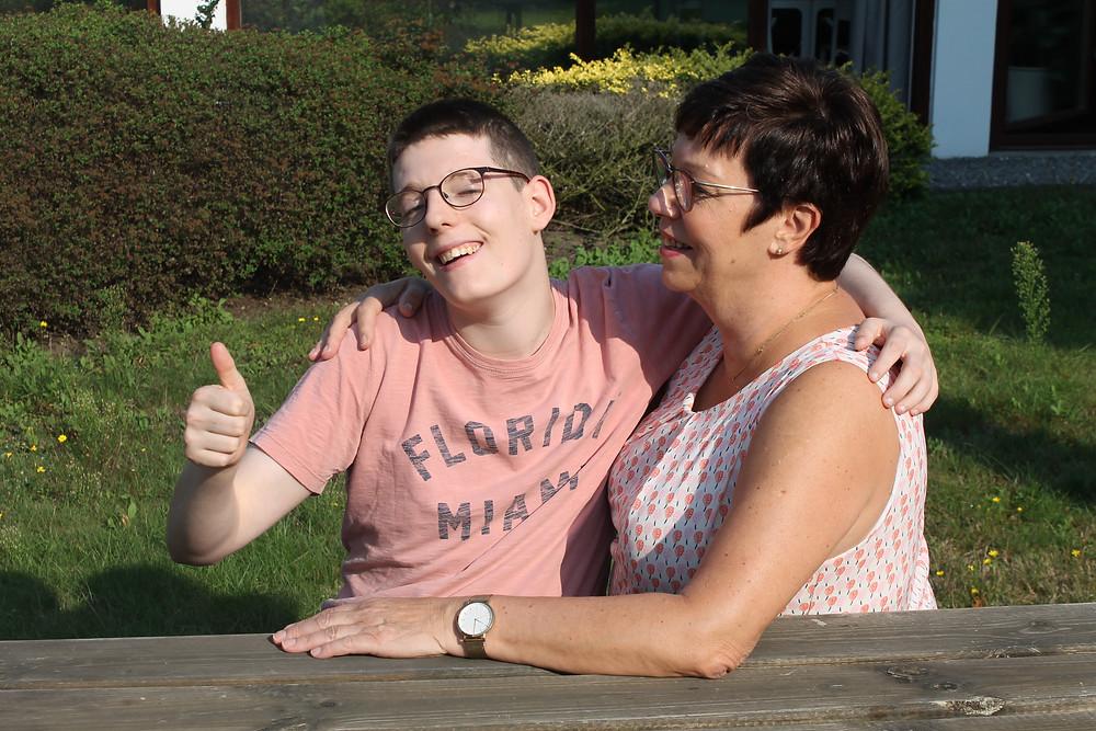 Lachende medewerker van Ter Heide omarmt bewoner met een beperking die een duim opsteekt