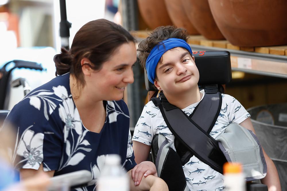 Bewoner Sander zit tevreden in zijn rolstoel naast zijn mama