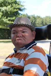 Volwassen bewoner van Ter Heide zit buiten in een rolstoel