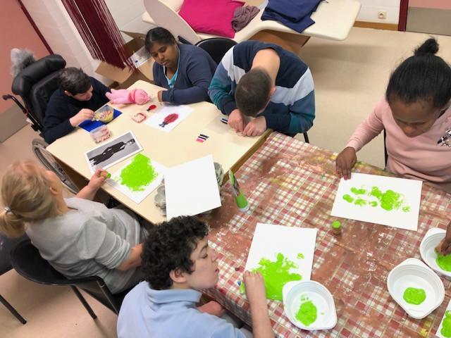 6 mensen met een beperking maken knutselwerken met groene verf