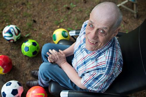 Bewoner van Ter Heide zit in een rolstoel, omringd door voetballen
