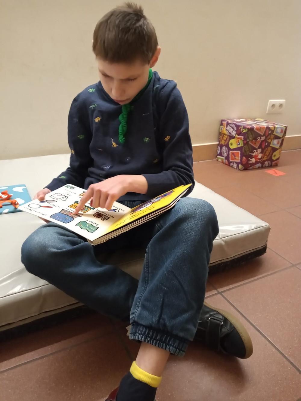Jonge bewoner leest een kinderboek terwijl hij op een mat zit