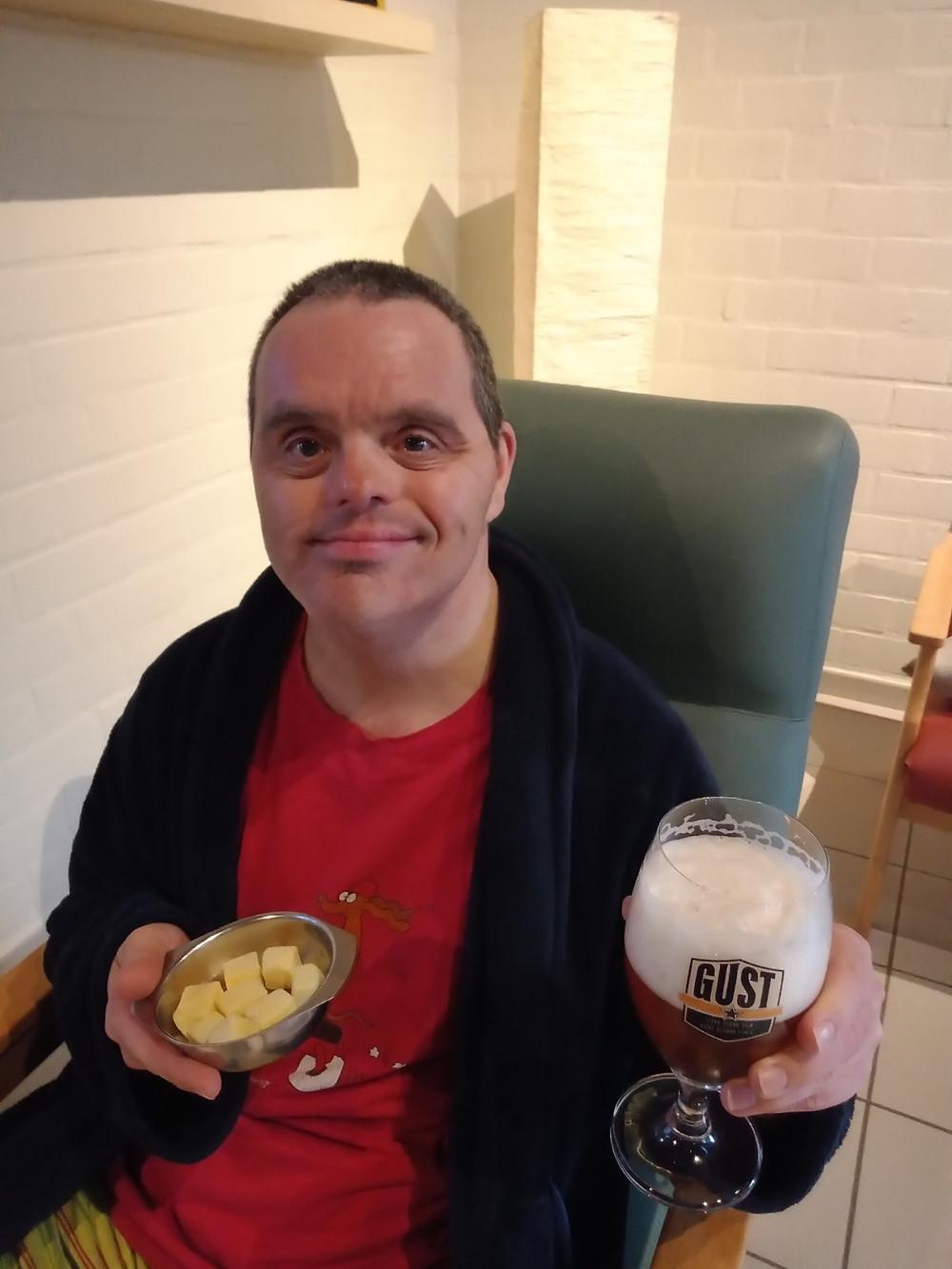Bewoner Dirk zit in een zetel met een pintje in de ene hand en kom met kaasblokjes in de andere hand