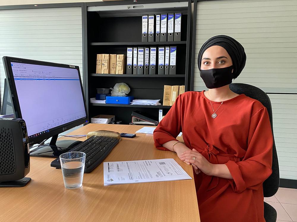 Stagiaire Nur zit aan haar computer in de financiële dienst