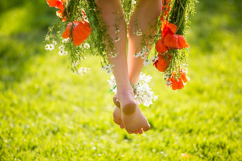 Woman legs on green grass with flower dr