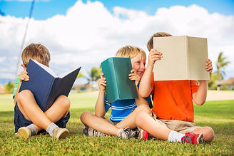 Group of Happy Kids Reading Books Outsid