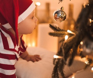 baby in a santa hat gazes at christmas tree ornament