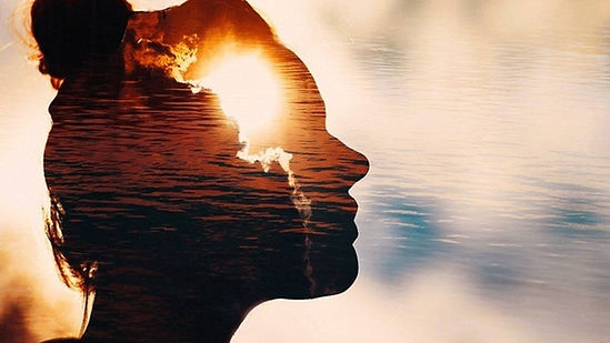 Image of woman superimposed over sunset clouds