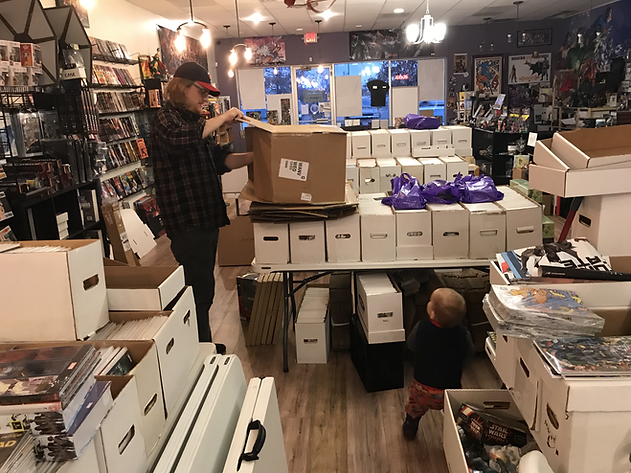Shop owner Jason and toddler son work among stacks of comic boxes