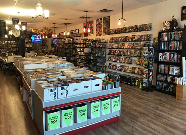 The interior of our shop, display of half off graphic novels, and 99 cent comic books are prominently displayed