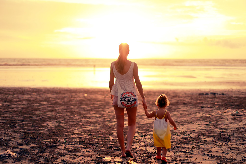 Woman and daughter enjoying freedom and view of the sun