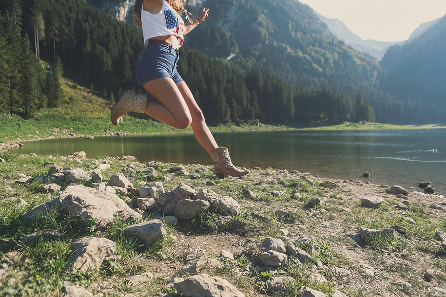 Carefree woman with USA shirt jumping by lake
