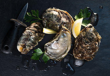 Opened oysters on stone slate plate with