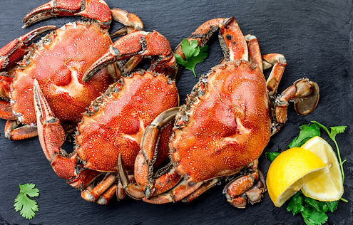 Cooked crabs on black plate served with