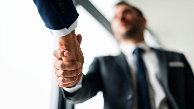 Dois homens se cumprimentando com aperto de mãos