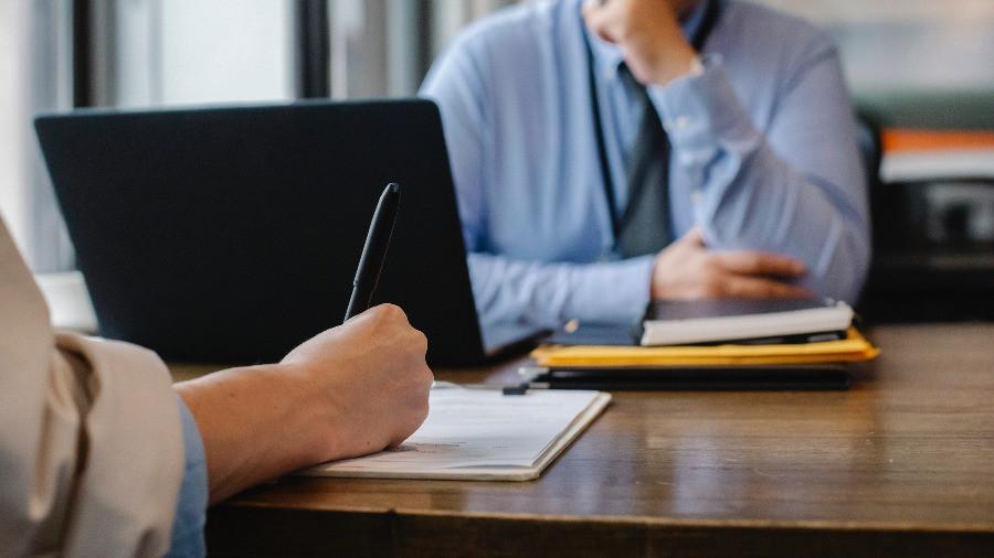 Pessoa assinando contrato e gestor observando