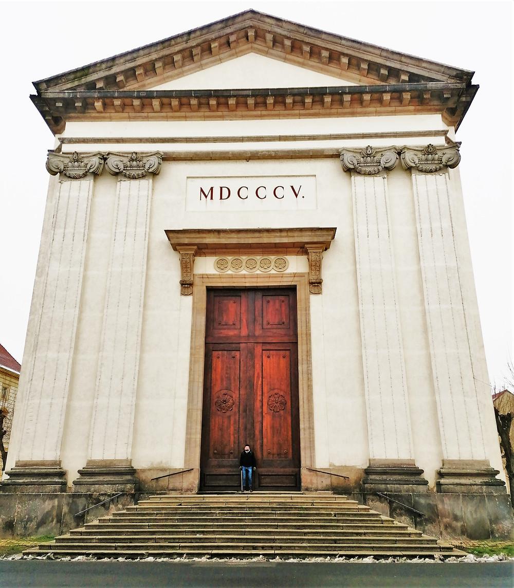 Kostela Vzkříšení Páně v Terezíně vyniká obrovskými vzletnými dveřmi, vedle kterých je člověk skutečně ztracený