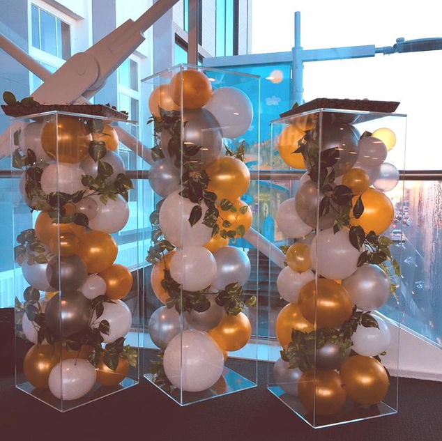 Acrylic plinths with balloons and foliage