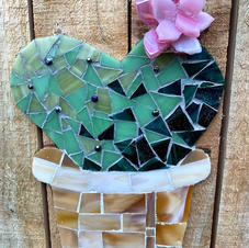 Mosaic cactus on wooden fence.