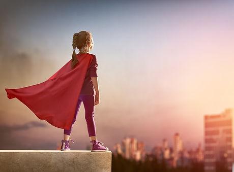 Little child girl plays superhero. Child on the background of sunset sky. Girl power concept.jpg
