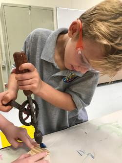 Boy using hand drill