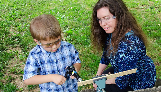 Jennie Harriman teaches woodworking to a child