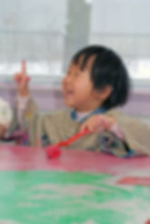 Preschool child painting on a table with a roller