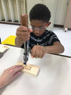 Kid using hand drill