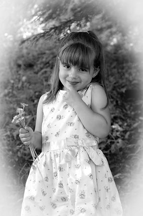 Black and white portrait of preschool girl outside with flowers